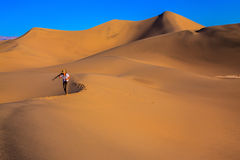 Woman is among sand dunes. Sunrise in the orange sands of the desert Mesquite Flat, USA. Woman - photographer is among the gently sloping sand dunes Royalty Free Stock Photos