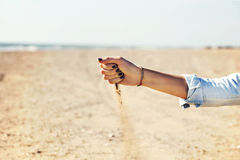 Woman with sand falling through her hands on the beach Royalty Free Stock Photography