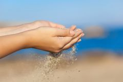 Woman with sand falling through her hands Royalty Free Stock Images