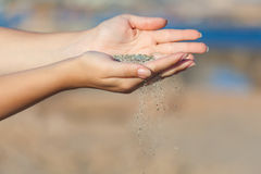 A woman with sand falling through her hands Royalty Free Stock Image