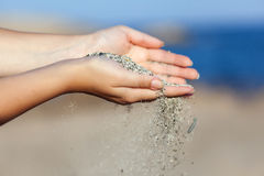 A woman with sand falling through her hands Royalty Free Stock Photo