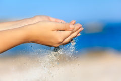 A woman with sand falling through her hands Royalty Free Stock Photography