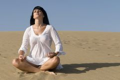 Woman in the sand in meditation position Stock Image