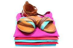 Woman sandals on pile of colorful clothes. White background Royalty Free Stock Photos