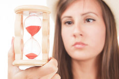 Woman with sandclock. Time passing concept, woman looking at sandclock Royalty Free Stock Photography
