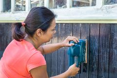 Woman sanding wood of house Stock Images