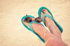 Woman sandy bare feet with flip flops and sunglasses Stock Image