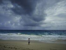 Woman on a sandy beach on a cloudy day Royalty Free Stock Photos