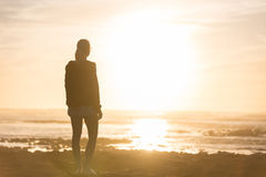 Woman on sandy beach watching sunset. Royalty Free Stock Images
