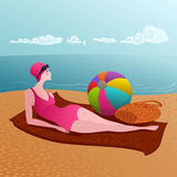 Woman on a sandy beach. Young woman relaxing on a sandy beach after a swim Royalty Free Stock Images