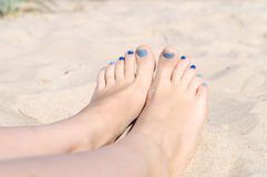 Woman sandy feet with blue nails pedicure Royalty Free Stock Image