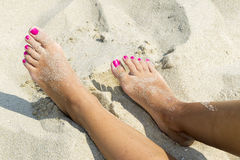 Woman sandy feet. With nail polish on beach royalty free stock photo