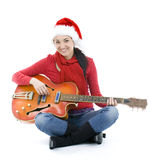 Woman in Santa cap playing electric guitar Royalty Free Stock Photos