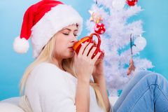 Woman in santa christmas hat drinking tea or coffee Royalty Free Stock Photography