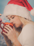 Woman in santa christmas hat drinking tea or coffee Royalty Free Stock Photo