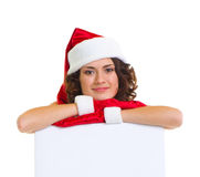 Woman in Santa Claus clothes leaning on blank boar Royalty Free Stock Images