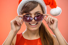 Woman in Santa Claus clothes with sunglasses Royalty Free Stock Image