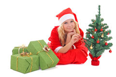 Woman in santa claus costume with gift and tree Stock Photos