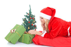 Woman in santa claus costume with gift and tree Stock Images