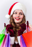 Woman in Santa Claus costume holds shopping bags Stock Photo