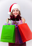 Woman in Santa Claus costume holds shopping bags Royalty Free Stock Images