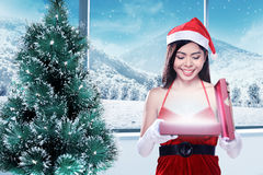 Woman in santa claus costume opening gift box Stock Photos