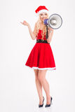 Woman in santa claus dress with megaphone pointing away Royalty Free Stock Images