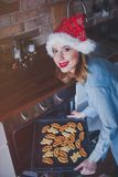 Woman in Santa Claus hat with baking tray Royalty Free Stock Images