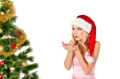 Woman in santa claus hat blows on open hands Stock Photos
