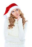 Woman in Santa Claus hat deeply deeply thinking. Beautiful woman in Santa Claus hat deeply deeply thinking Royalty Free Stock Photography