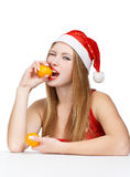 Woman in santa claus hat eating mandarins. Young woman in santa claus hat holding mandarins in hands isolated on white background Stock Photography
