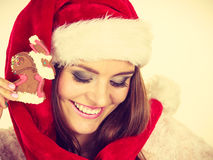 Woman santa claus hat with gingerbread cookie. Christmas Stock Images
