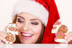 Woman santa claus hat with gingerbread cookies. Christmas Stock Photo