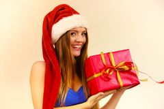 Woman in santa claus hat holds gift box. Christmas time. Lovely smiling woman wearing santa claus hat holding big red christmas present gift. Xmas, happiness Royalty Free Stock Image