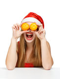 Woman in santa claus hat joking with mandarins. Cheerful laughing young woman in santa claus hat holding a mandarins like eyes as a joke isolated on white Royalty Free Stock Image