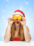 Woman in santa claus hat joking with mandarins. Cheerful young woman in santa claus hat holding a mandarins like eyes as a joke on blue snowfall background Royalty Free Stock Image