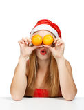 Woman in santa claus hat joking with mandarins. Cheerful young woman in santa claus hat holding a mandarins like eyes as a joke isolated on white background Stock Images