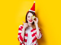 Woman in Santa Claus hat with little alarm clock Royalty Free Stock Photography