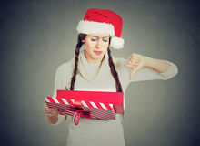 Woman in santa claus hat opening gift upset showing thumbs down. Young woman in red santa claus hat opening gift, very upset at what she received, showing thumbs royalty free stock image