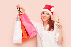 Woman in Santa Claus hat with shopping bags Stock Images