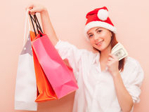 Woman in Santa Claus hat with shopping bags Stock Photos