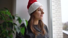 Beautiful young woman in the Santa Claus hat sitting on window sill with tea and reading book in anticipation of stock video