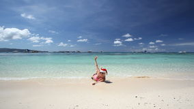 Woman in Santa Claus hat sitting on tropical beach. Boracay, Philippines stock video footage