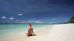 Woman in Santa Claus hat sitting on tropical beach. Boracay, Philippines stock video