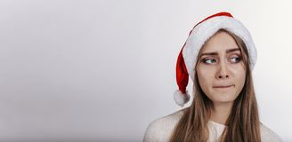Woman in santa claus hat spread wide her hands and looking at camera with embarrassing face. Pretty young model with blonde long hair, wide eyebrows and blue Stock Photo