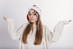 Woman in santa claus hat spread wide her hands and looking at camera with embarrassing face. Pretty young model with blonde long hair, wide eyebrows and blue Royalty Free Stock Photography