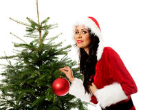 Woman with santa clothes decorating christmas tree Stock Photography