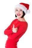 Woman in santa clothes gesturing thumbs up Stock Photos