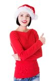 Woman in santa clothes gesturing thumbs up Stock Images