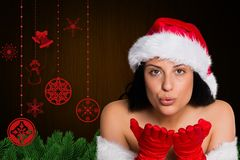 Woman in santa costume blowing a kiss Royalty Free Stock Image